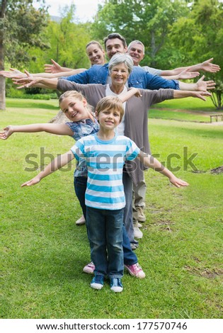 Portrait of a happy extended family standing in row with arms outstretched at the park - stock photo