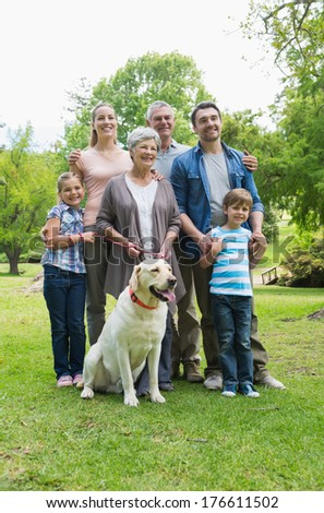 Portrait of a happy extended family with pet dog standing at the park - stock photo
