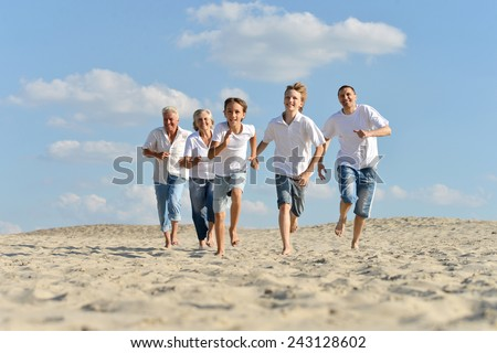Portrait of a happy family a running barefoot in the sand in the summer