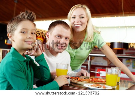 Portrait of a happy family having lunch at the cafe - stock photo