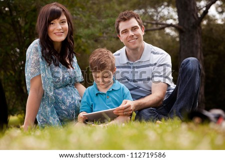 Portrait of a happy family in a park using a digital tablet - stock photo