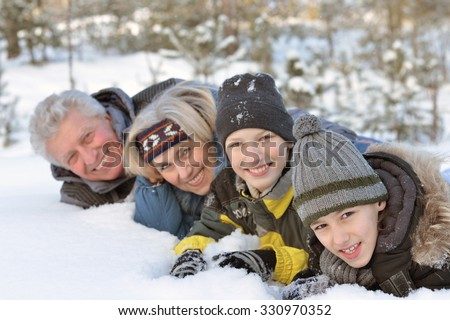 Portrait of a happy family in winter snowy park - stock photo