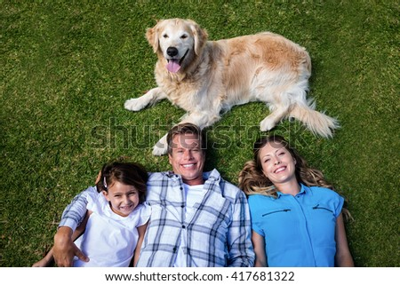Portrait of a happy family lying on grass with their dog - stock photo
