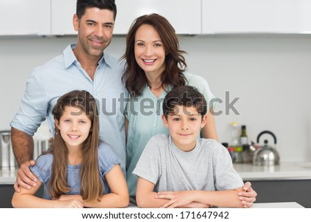 Portrait of a happy family of four in the kitchen at home - stock photo