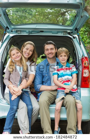 Portrait of a happy family of four sitting in car trunk while on picnic - stock photo