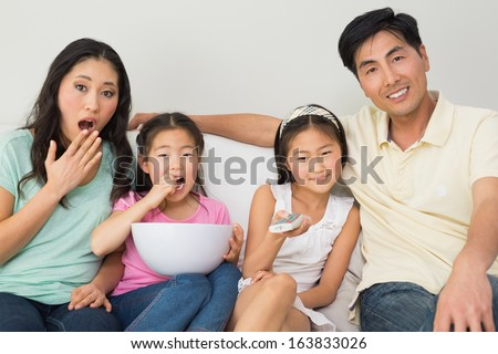 Portrait of a happy family of four watching tv in the living room at home - stock photo