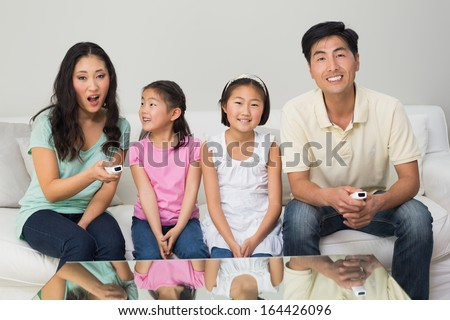 Portrait of a happy family of four watching tv in the living room at home