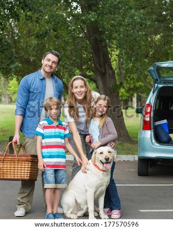 Portrait of a happy family of four with car at picnic - stock photo