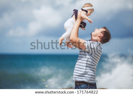 portrait of a Happy family of man and child having fun by the blue sea in summertime - stock photo