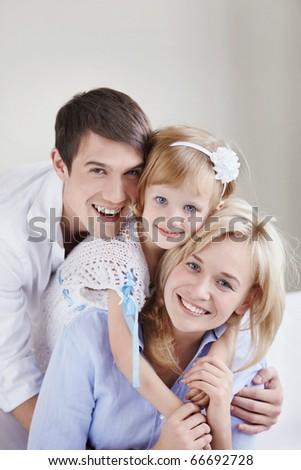 Portrait of a happy family of three - stock photo