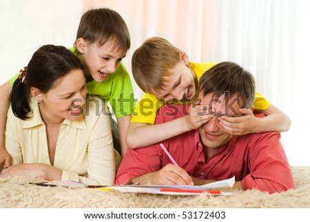 portrait of a happy family playing on the carpet