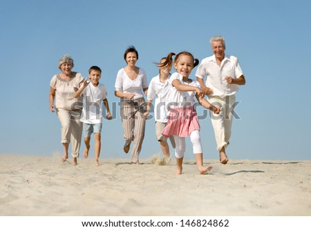 portrait of a happy family running barefoot in the sand in the summer - stock photo