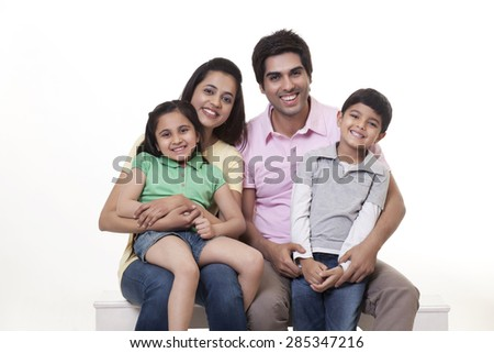 Portrait of a happy family sitting on bench over white background - stock photo