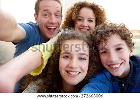 Portrait of a happy family taking a selfie together - stock photo