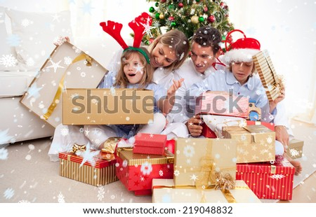 Portrait of a happy family unpacking Christmas presents against snow - stock photo