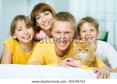 Portrait of a happy family with a house cat looking at camera - stock photo