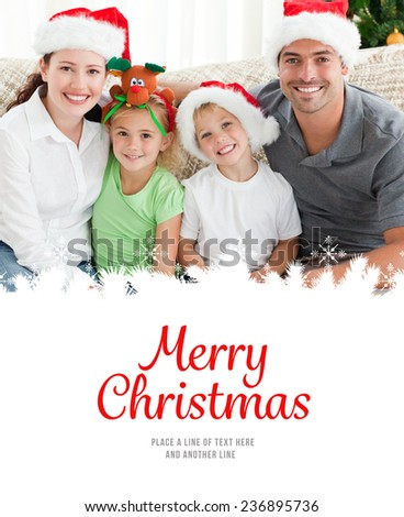Portrait of a happy family with Christmas hats sitting on the sofa against merry christmas - stock photo