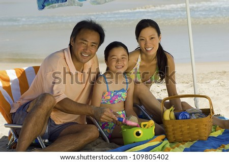 Portrait of a happy family with daughter on a beach vacation - stock photo