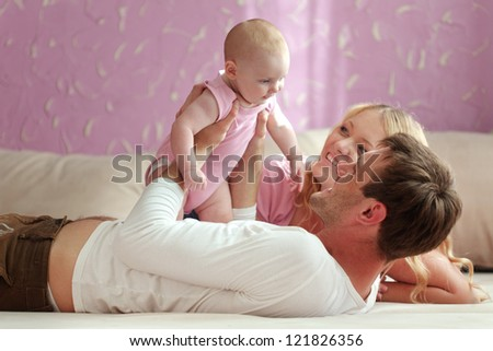 Portrait of a happy family with their baby daughter - stock photo