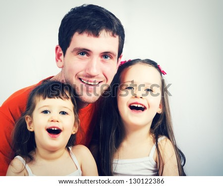 Portrait of a happy father and two beautiful little girls - stock photo
