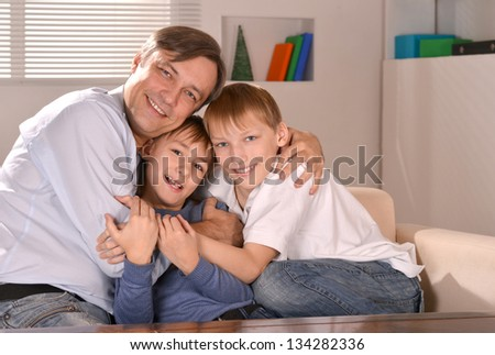 portrait of a happy father hugging his sons - stock photo