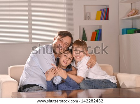 portrait of a happy father hugging his sons