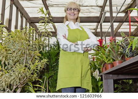Portrait of a happy female gardener standing with arms crossed in botanical garden - stock photo