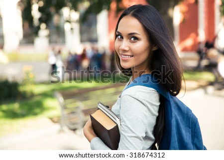 Portrait of a happy female student looking back at camera outdoors - stock photo