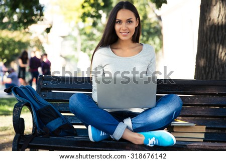 Portrait of a happy female student sitting on the bench with laptop outdoors and looking at camera - stock photo