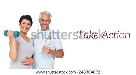 Portrait of a happy fit couple with dumbbell and water bottle white background - stock photo