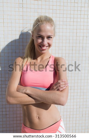 Portrait of a happy fit woman dressed in sportswear enjoy rest after workout in sunny summer day, young female jogger with a bright smile looking at camera while taking break after fitness training - stock photo