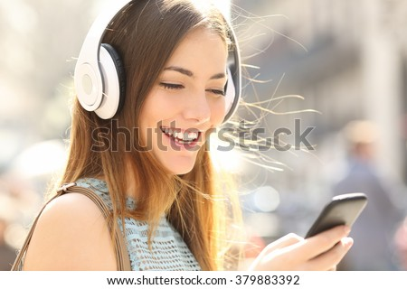 Portrait of a happy girl listening music on line with wireless headphones from a smartphone in the street in a summer sunny day - stock photo