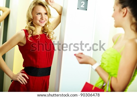 Portrait of a happy girl looking at her friend in clothing department - stock photo