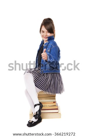 Portrait of a happy girl sitting on a pile of books and showing ok sign over white background - stock photo