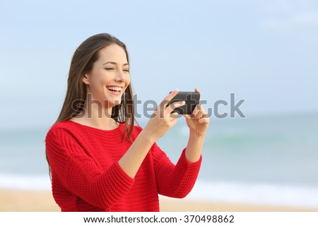 Portrait of a happy girl wearing red sweater laughing while watching streaming videos in smart phone on the beach with the ocean and a a warm light - stock photo