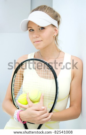 portrait of a happy girl with a tennis racket - stock photo