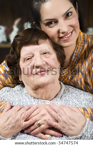 Portrait of a happy grandma and granddaughter sitting in a hug with  their hands together in living room - stock photo