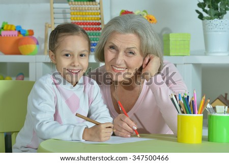 Portrait of a happy grandmother with granddaughter drawing together - stock photo