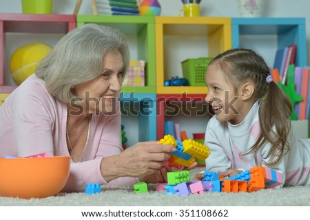 Portrait of a happy grandmother with granddaughter playing together - stock photo