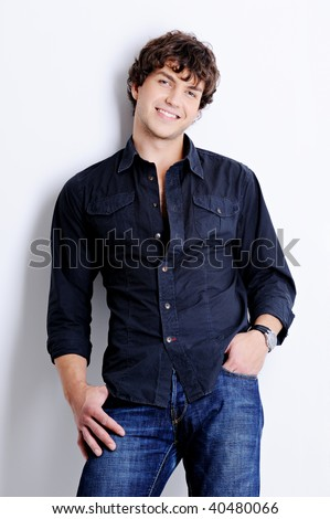 Portrait of a happy handsome young man posing in  studio with beautiful curly hairs - stock photo
