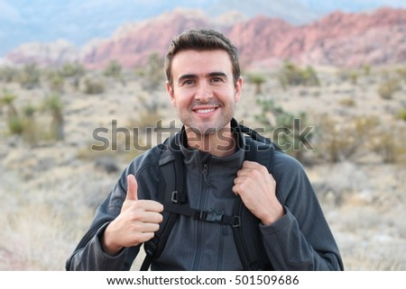 Portrait of a happy hiker giving a thumbs up in nature
