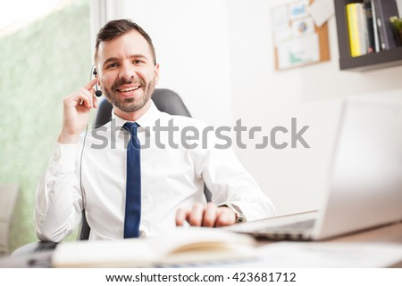 Portrait of a happy Hispanic telemarketer wearing a headset and smiling to customers while sitting at an office - stock photo