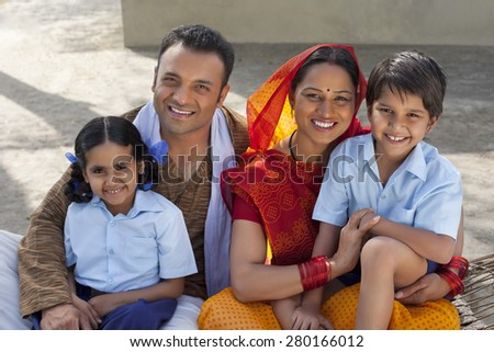 Portrait of a happy Indian family of four sitting on cot - stock photo