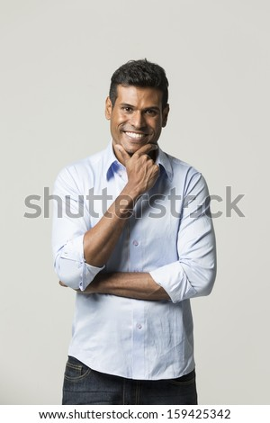 Portrait of a happy Indian man standing in front of a light grey background.  - stock photo