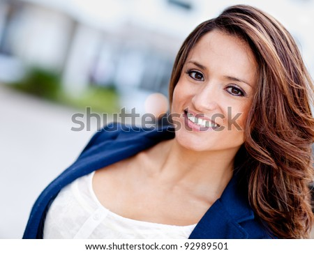 Portrait of a happy Latin woman outdoors - stock photo