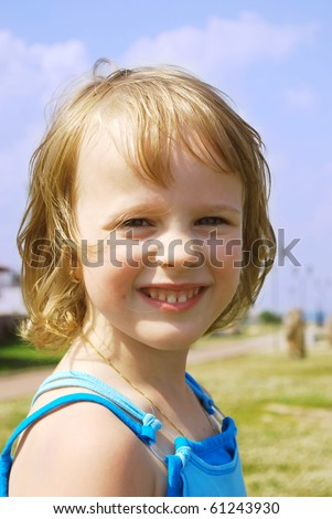 Portrait of a happy liitle girl on the green grass  background.