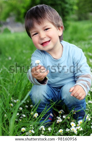 Portrait of a happy little boy in the park - stock photo