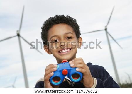 Portrait of a happy little boy with binoculars at wind farm - stock photo