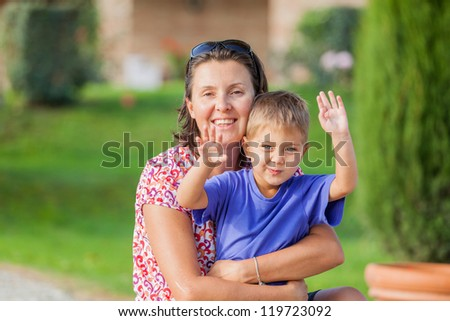 Portrait of a happy little boy with his mother in the garden - stock photo