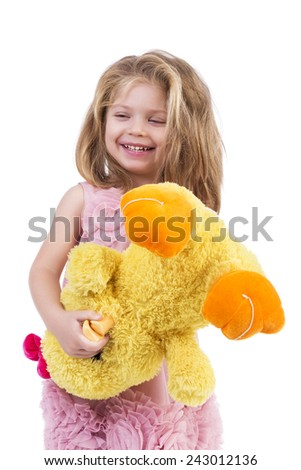 Portrait of a happy little girl holding a yellow plush toy over white background - stock photo